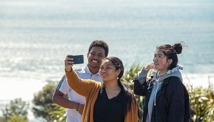 Students taking a selfie by Raglan Beach